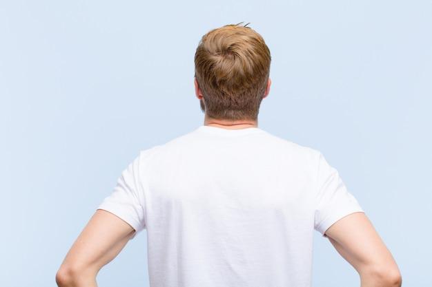 Junger blonder erwachsener mann, der verwirrt oder voll oder die zweifel und fragen, wundernd, mit den händen auf hüften, hintere ansicht glaubt