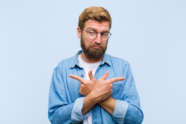 Junger blonder erwachsener mann, der verwirrt und verwirrt, unsicher schaut und in entgegengesetzte richtungen mit zweifeln zeigt