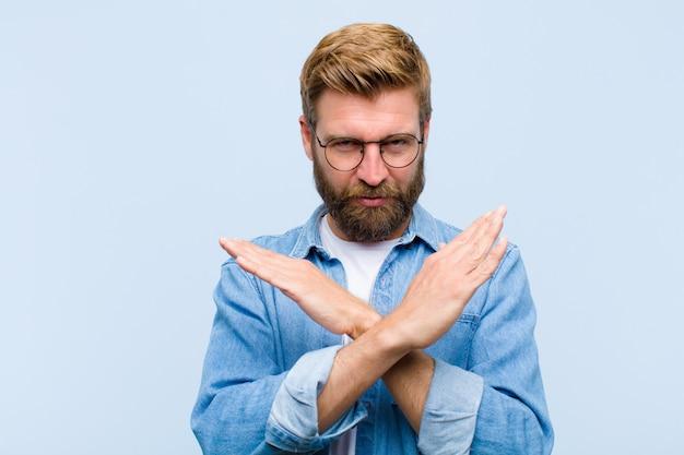 Junger blonder erwachsener mann, der von ihrer haltung gestört und krank schaut und genug sagt! hände nach vorne gekreuzt und fordern sie auf zu stoppen