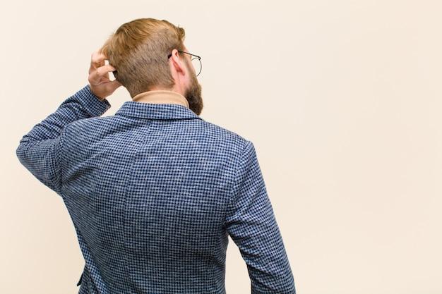 Junger blonder geschäftsmann, der ahnungslos und verwirrt sich fühlt und eine lösung, mit der hand auf hüfte und anderer auf kopf, hintere ansicht denkt