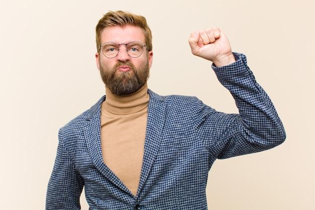 Junger blonder geschäftsmann, der ernst, stark und rebellisch sich fühlt, faust oben anhebt, für revolution protestiert oder kämpft