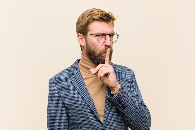 Junger blonder geschäftsmann, der um ruhe und ruhe bittet, mit dem finger vor mund gestikuliert, shh sagt oder ein geheimnis hält