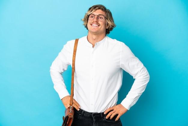 Junger blonder geschäftsmann lokalisiert auf blauem hintergrund, der mit den armen an der hüfte aufwirft und lächelt
