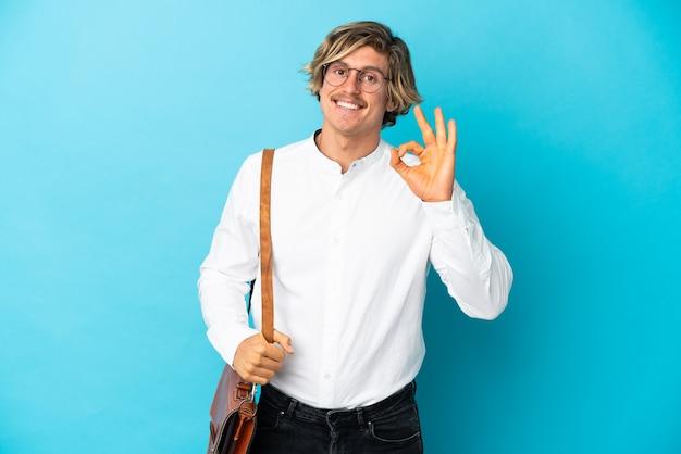 Junger blonder geschäftsmann lokalisiert auf blauem hintergrund, der ok zeichen mit den fingern zeigt