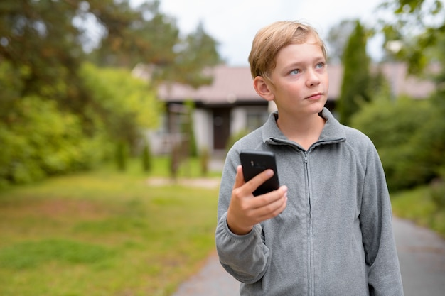 Junger blonder hübscher junge, der während des telefonierens zu hause heraus denkt