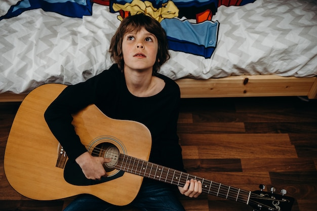 Junger blonder junge, der auf dem boden sitzt und eine gitarre hält