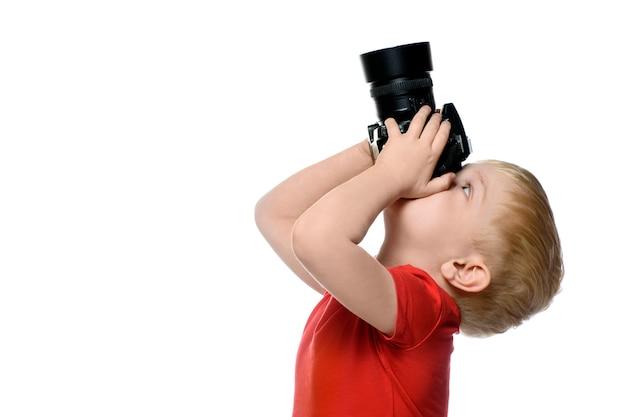 Junger blonder junge mit fotokamera