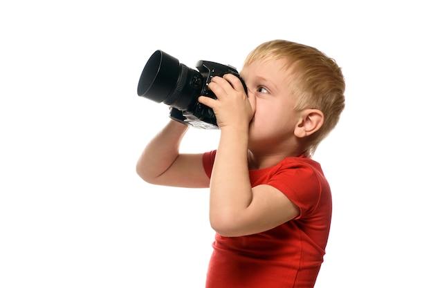 Junger blonder junge mit kamera. porträt, lokalisiert auf weißer wand. seitenansicht.