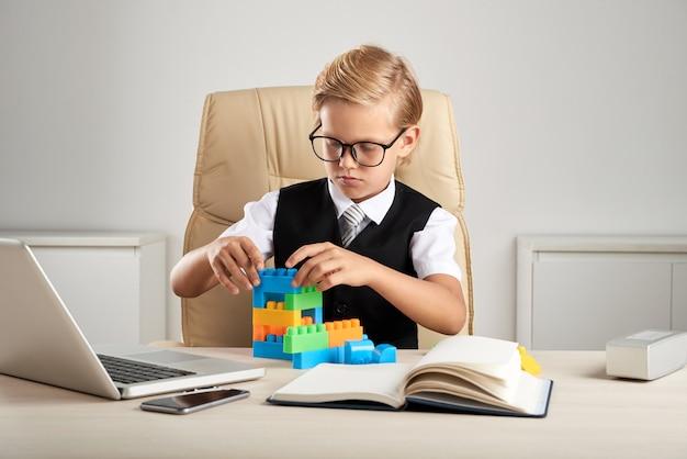 Junger blonder kaukasischer junge, der im exekutivstuhl im büro sitzt und mit bausteinen spielt