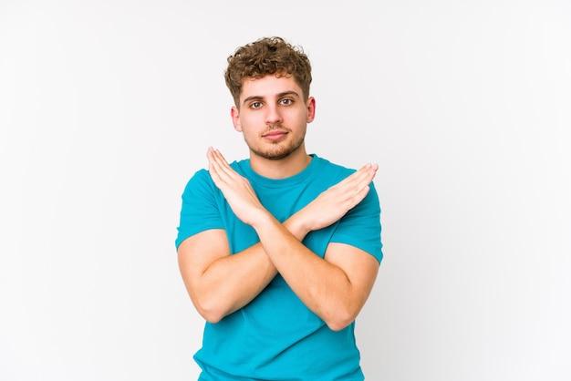 Junger blonder kaukasischer mann des lockigen haares, der zwei arme verschränkt hält