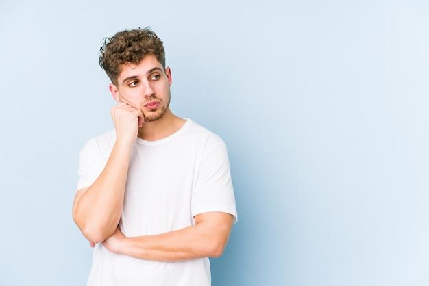 Junger blonder kaukasischer mann des lockigen haares isoliert, der sich traurig und nachdenklich fühlt und kopierraum betrachtet.