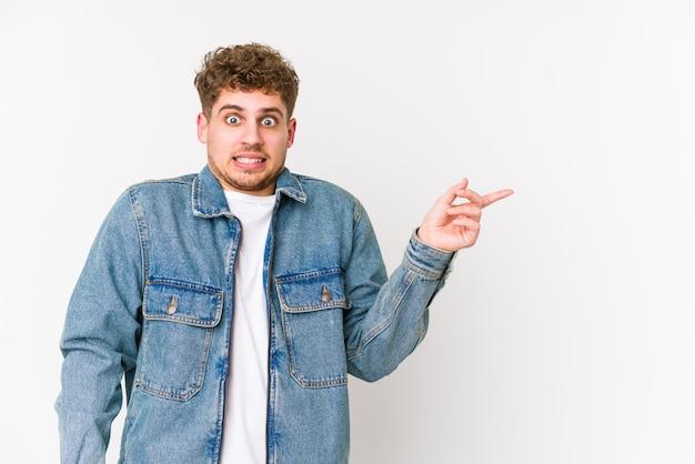 Junger blonder kaukasischer mann des lockigen haares isoliert schockiert, der mit zeigefingern auf einen kopienraum zeigt.