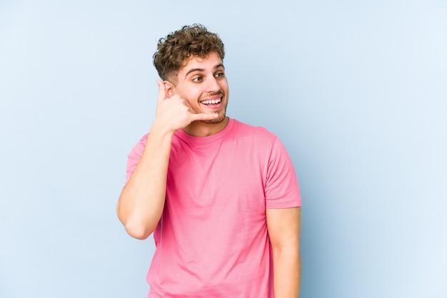 Junger blonder kaukasischer mann des lockigen haares lokalisiert, der eine handy-anrufgeste mit fingern zeigt.