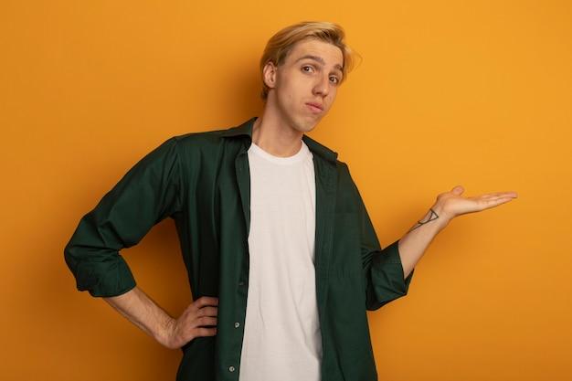 Junger blonder kerl, der grünes t-shirt trägt, das vorgibt, etwas zu halten, das hand auf hüfte legt