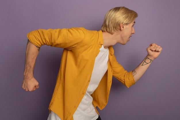 Junger blonder kerl, der in der profilansicht steht und gelbes t-shirt trägt, das laufende geste lokalisiert auf purpur zeigt