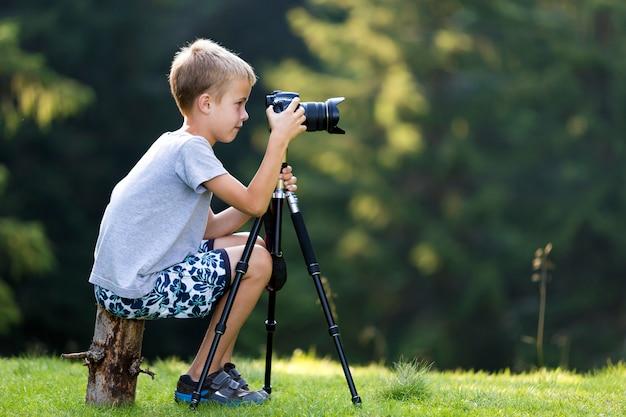 Junger blonder kinderjunge, der auf baumstumpf auf der grasartigen reinigung macht foto mit stativkamera sitzt.
