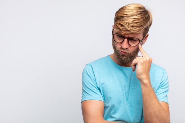 Junger blonder mann denkt oder zweifelt an ausdruck