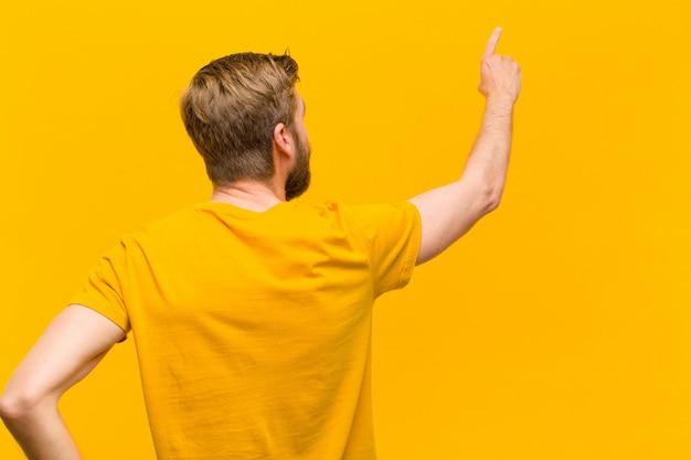 Junger blonder mann, der auf gegenstand auf kopienraum, hintere ansicht steht und zeigt