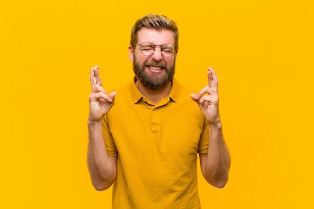 Junger blonder mann, der besorgt beide finger kreuzt, sich besorgt fühlt und gutes glück wünscht oder hofft