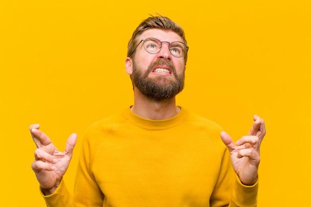 Junger blonder mann, der besorgt finger kreuzt und auf gutes glück mit einem besorgten blick gegen orange wand hofft