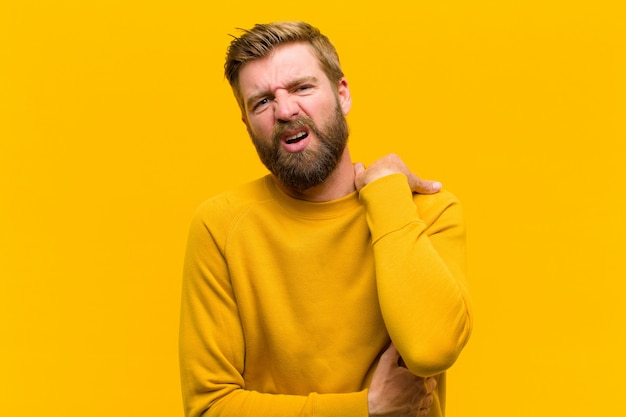 Junger blonder mann, der besorgtem krankem krankem und unglücklichem leiden eines schmerzlichen magenschmerzes oder der grippe sich fühlt