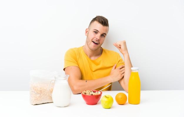 Junger blonder mann, der die starke geste machend frühstückt