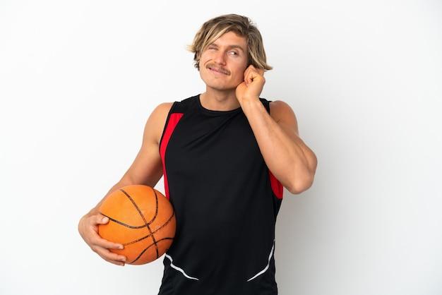 Junger blonder mann, der eine kugel des basketballs lokalisiert auf weißem hintergrund frustriert hält und ohren bedeckt