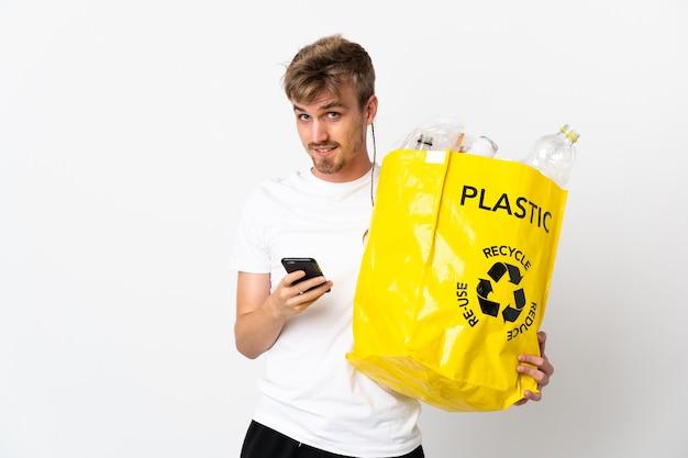 Junger blonder mann, der eine recycling-tasche voll papier hält, um lokalisiert auf weißer wand zu recyceln, die eine nachricht mit dem handy sendet