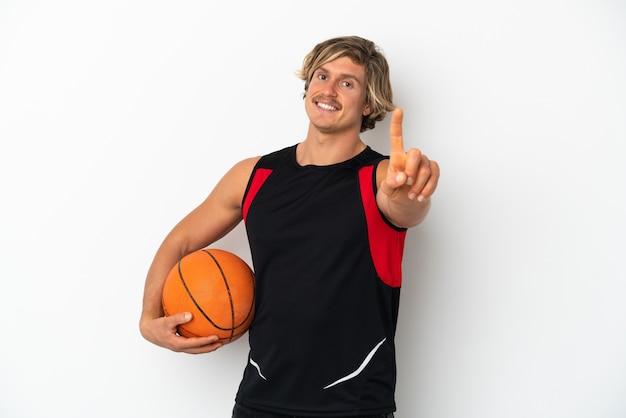 Junger blonder mann, der einen basketballball hält, der auf weißem hintergrund lokalisiert wird, der einen finger zeigt und anhebt