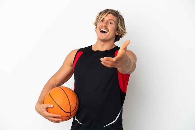 Junger blonder mann, der einen basketballball lokalisiert auf weißer wand hält händeschütteln für das schließen eines guten geschäfts hält