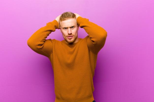 Junger blonder mann, der einen pullover trägt, der sich frustriert und genervt fühlt, krank und müde vom versagen, satt von langweiligen aufgaben