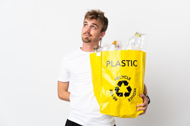 Junger blonder mann, der einen recyclingbeutel voll papier hält, um isoliert zu recyceln
