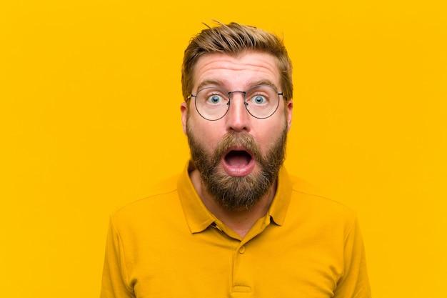 Junger blonder mann, der erschrocken und entsetzt sich fühlt, wenn der mund in der überraschung gegen orange wand weit offen ist