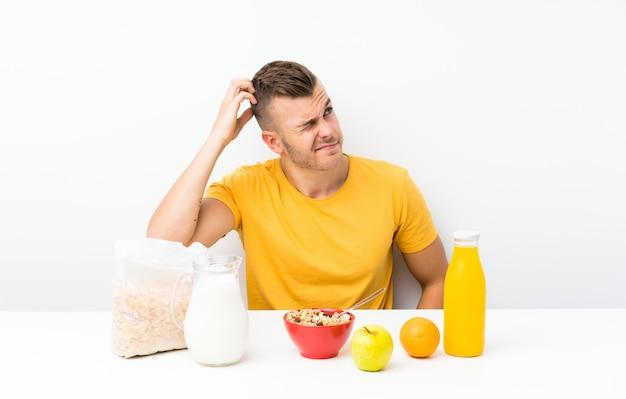 Junger blonder mann, der frühstückt, zweifel habend und mit verwirren gesichtsausdruck