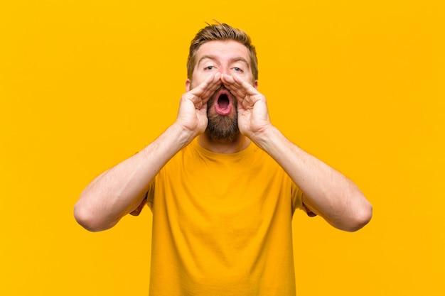 Junger blonder mann, der glücklich, aufgeregt und positiv sich fühlt und einen großen ruf heraus mit den händen nahe bei dem mund gibt und orange wand ausruft