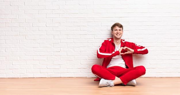 Junger blonder mann, der lächelt und sich glücklich, süß, romantisch und verliebt fühlt und herzform mit beiden händen macht, die auf dem boden sitzen