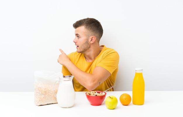 Junger blonder mann, der mit dem zeigefinger zurück zeigend frühstückt