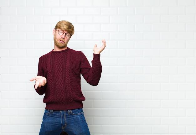 Junger blonder mann, der mit einem dummen, verrückten, verwirrten, verwirrten ausdruck zuckt, sich genervt und ahnungslos gegen vintage-fliesenwand fühlt