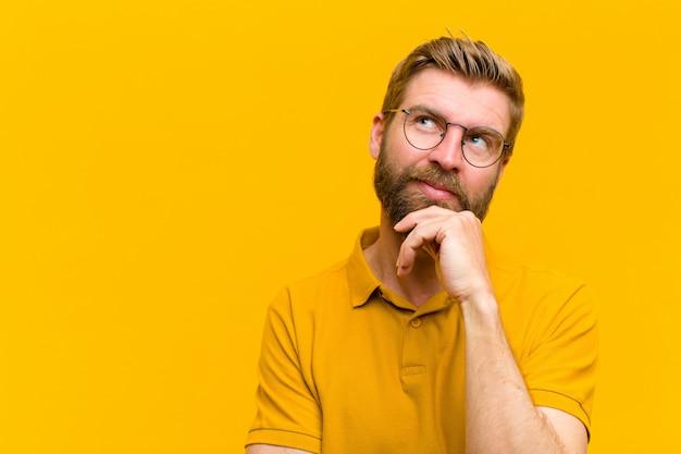 Junger blonder mann, der nachdenklich sich fühlt, ideen sich wundert oder sich vorstellt, oben zum copyspace gegen orange wand träumt und schaut