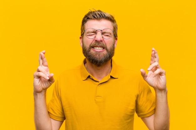 Junger blonder mann, der nervös und hoffnungsvoll sich fühlt, finger kreuzt, für gutes glück gegen orange wand betet und hofft