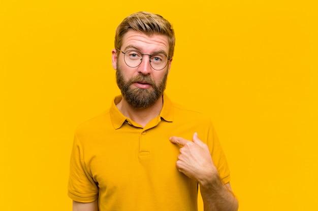 Junger blonder mann, der sich verwirrt, verwirrt und unsicher fühlt, auf sich selbst zeigt und fragt, wer, ich? orange wand