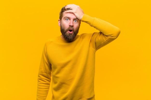 Junger blonder mann, der über einer vergessenen frist in panik gerät, betont glaubt und eine verwirrung oder einen fehler auf orange wand vertuschen muss