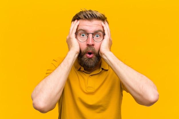 Junger blonder mann, der unangenehm entsetzt, ängstlich oder besorgt aussieht, mund weit offen