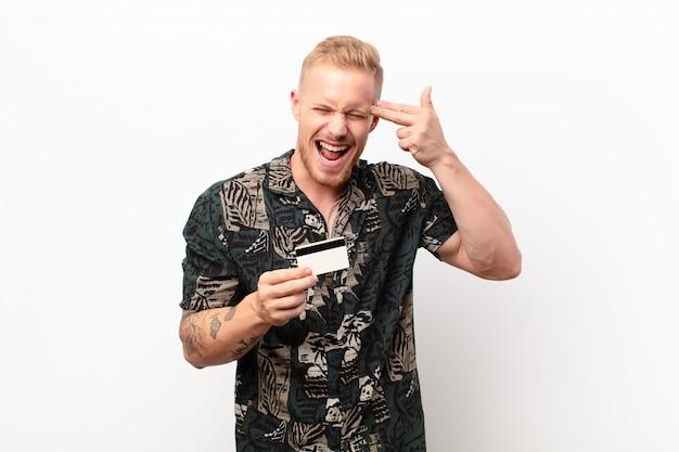 Junger blonder mann, der unglücklich und gestresst aussieht, selbstmordgeste, die waffenzeichen mit hand macht, zeigt mit einer kreditkarte auf kopf