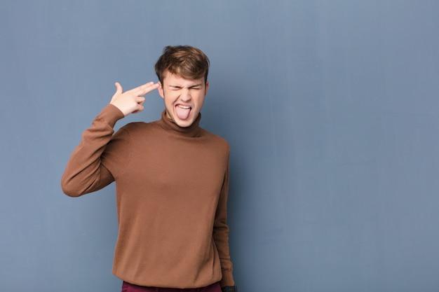 Junger blonder mann, der unglücklich und gestresst schaut, selbstmordgeste, die waffenzeichen mit hand macht, zeigt auf kopf, der gegen flache wand isoliert ist