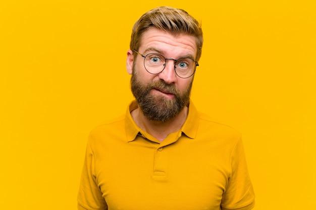 Junger blonder mann, der verwirrt und, beißende lippe mit einer nervösen geste verwirrt schaut und nicht die antwort auf das problem gegen orange wand kennt