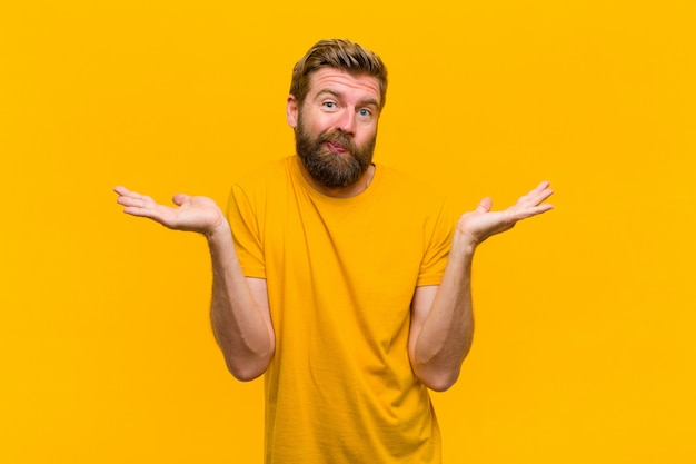 Junger blonder mann, der verwirrt und verwirrt sich fühlt, verschiedene wahlen mit lustigem ausdruck auf orange wand zweifelt, belastet oder wählt