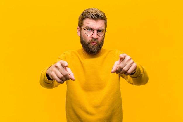 Junger blonder mann, der vorwärts auf kamera mit beiden fingern und verärgertem ausdruck zeigt
