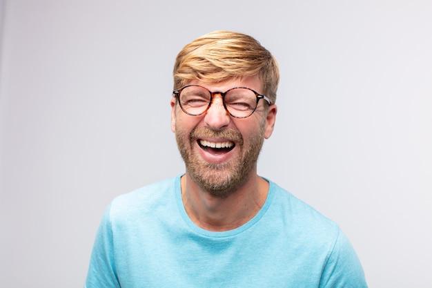 Junger blonder mann glücklich und lächelnd. zufriedener ausdruck