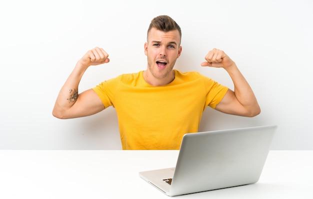 Junger blonder mann in einer tabelle mit einem laptop einen sieg feiernd